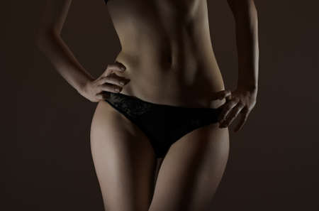 Front view of slim female body in black panties. Stock Photo