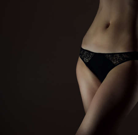 bodyscape: Front view of sexual female body in black panties. Space for text