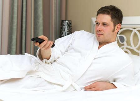 Man in bathrobe watching TV in hotel room.