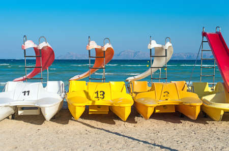 Pedal-boats with water slides on the beach. Stock Photo