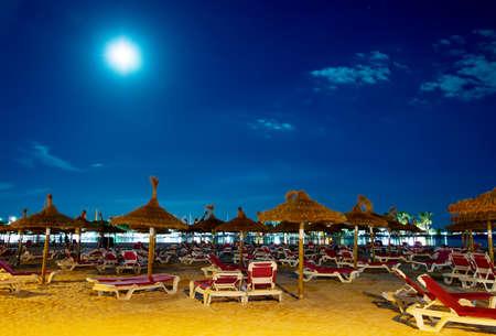 Night beach with sun loungers in Alcudia, Mallorca.