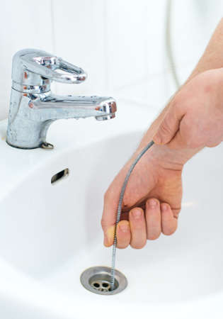 Plumber repairing sink with plumber's snake. 免版税图像