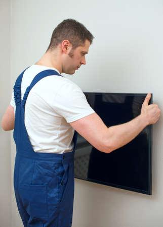 벽에 TV를 장착하는 사람. 스톡 콘텐츠
