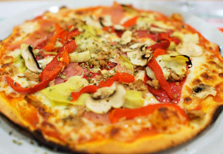Pizza with ham, paprika and mushrooms.