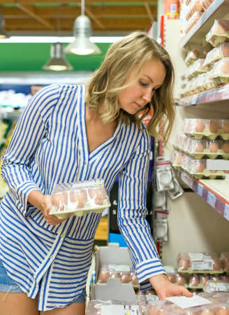 Young woman is choosing eggs in supermarket. Stock Photo