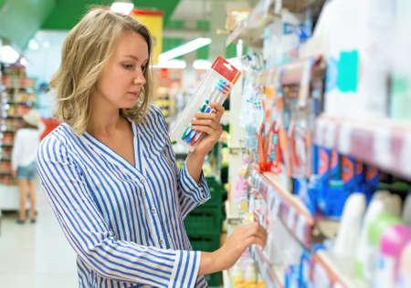 Young woman is choosing toothbrush in supermarket. Reklamní fotografie - 74766271