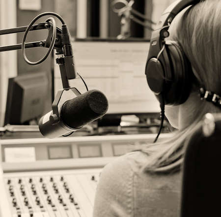 Rear view of female dj working in front of a microphone on the radio photo