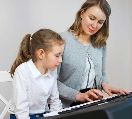 ピアノを弾く少女を教える女性。 写真素材 - 78028094