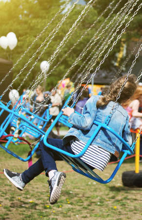 Little girl is riding a carousel in amusement park. Stock Photo