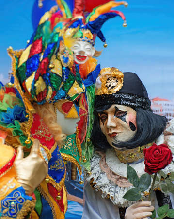 Unrecognizable people in venetian masks on street carnival.