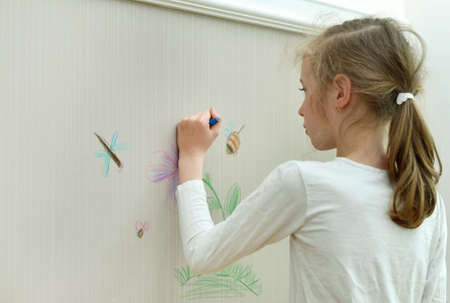 Little girl drawing on the wallpaper with pencil.