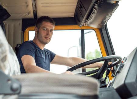 Mannelijke vrachtwagenchauffeur in cabine van zijn gele vrachtwagen.