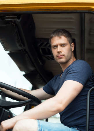 Male trucker in cabin of his yellow truck. Stock Photo