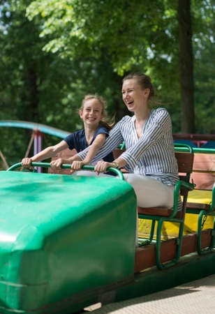 Little girl and her mother having fun on roller coaster. Stock Photo