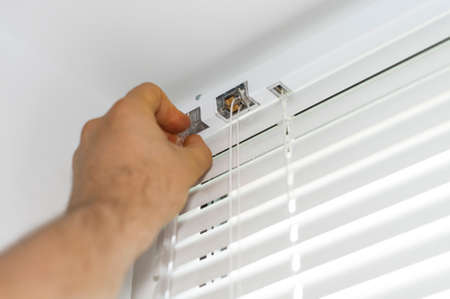 Man installing venetian blinds on windows.