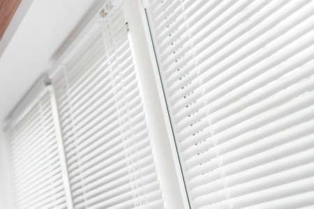 jalousie: Windows with white venetian blinds.