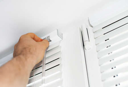 jalousie: Man installing venetian blinds on windows.