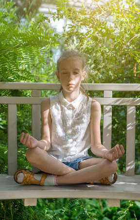 Cute little girl meditating in the garden. photo