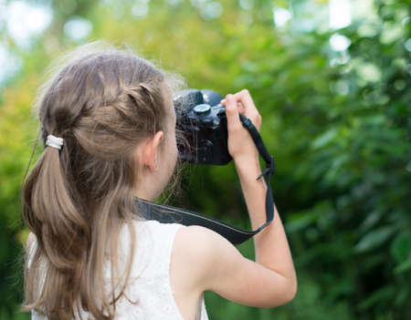 Cute little girl doing photographs of nature. photo