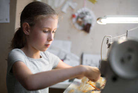 Little girl working on sewing machine at home. Stock Photo