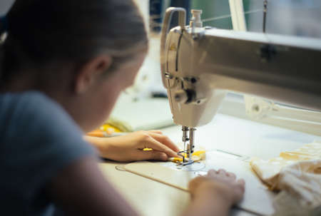 Little girl working on sewing machine at home. Close-up view. Archivio Fotografico
