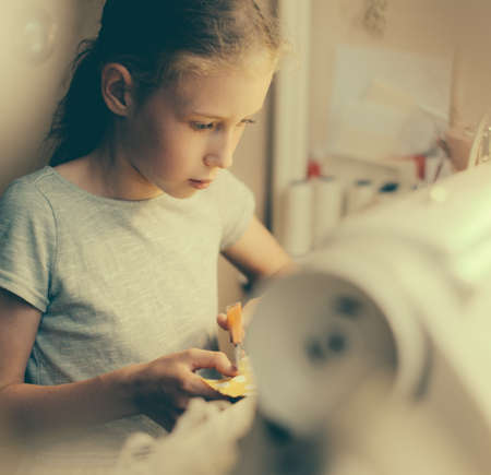 sewing machines: Little girl working on sewing machine at home. Stock Photo