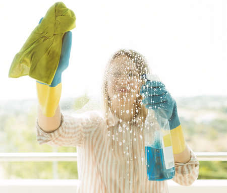 House cleaning. Woman is wiping glass on the balcony. Stock Photo