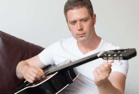 bel homme tuning une guitare à la maison