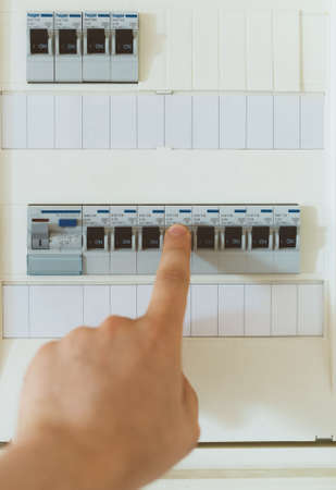 Male hand switching on fuse board. Stock Photo - 88122377