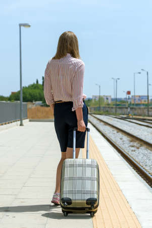 Woman with baggage is waiting for her train.