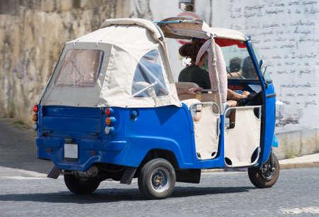 Auto rickshaw riding on the street. Stock Photo