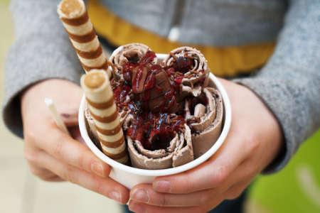 Child is holding hocolate ice cream. Foto de archivo