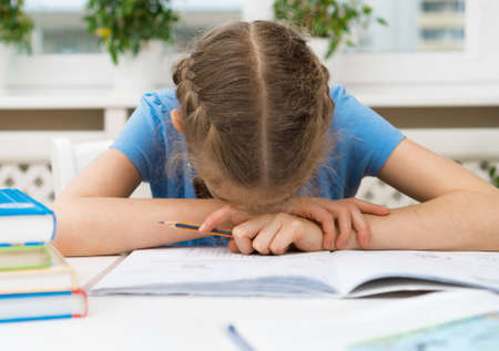 Little girl dont want to do her homework. Stock Photo