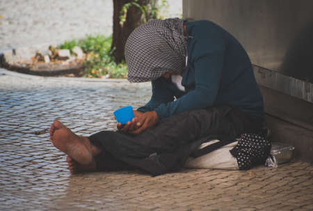 Homeless woman begs alms in the street.