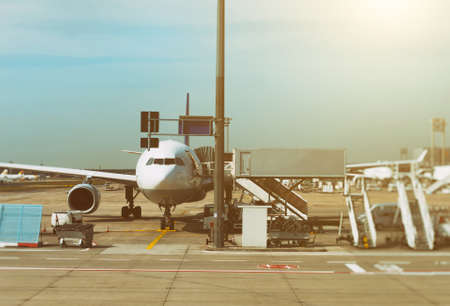 Passenger plane in the airport at sunrise. Aircraft maintenance. Editorial