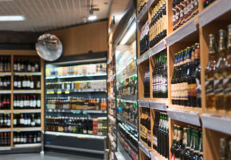Blurred image of shelves with alcoholic drinks in supermarket.