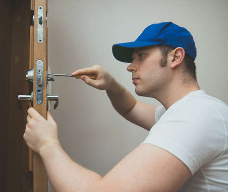 Young handyman in uniform changing door lock.