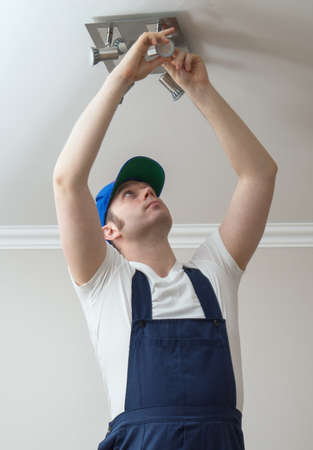 Handsome male electrician changing the light bulb.