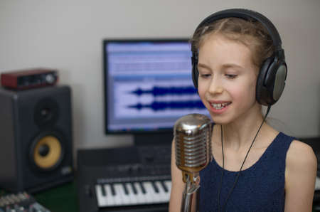 Little girl singing a song in home recording studio. Stok Fotoğraf