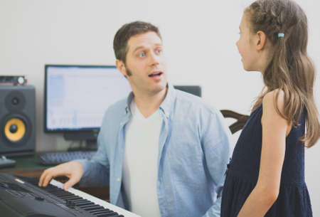 Male vocal coach teaching little girl how to sing. Focused on girl.