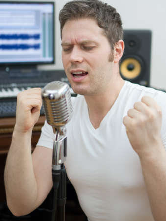 Handsome man rehearsing a song in the music studio.