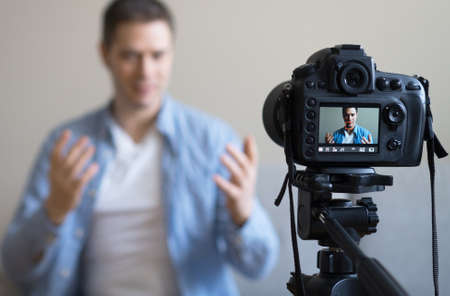 Handsome man making video blog. Focus on camera. Stockfoto