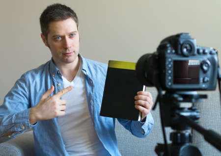 Handsome man making video blog about books and education.