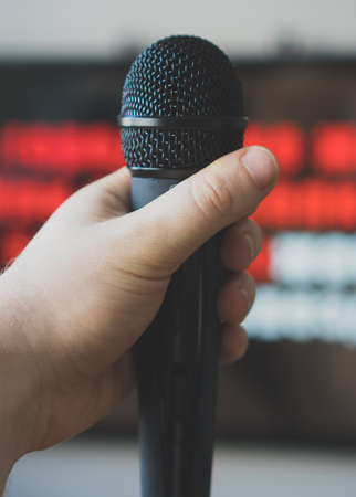 Man hand with karaoke microphone in front of TV.