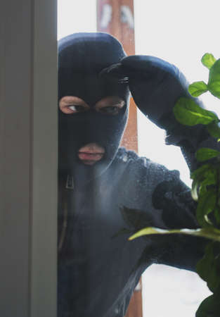 Thief in the mask looks through the window into the house. Stok Fotoğraf