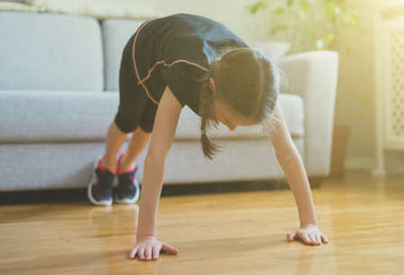 Little girl doing push ups at home. Gymnastics at home.