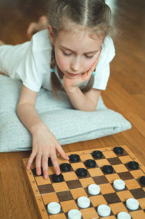 Little cute girl playing checkers board game. Stock Photo