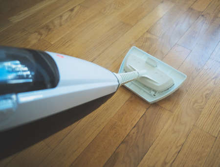 Cleaning the floor with a dry steam cleaner.