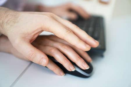Sexual harassment at work. Man touching secretarys hand. Stock Photo