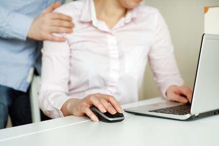 Sexual harassment at work. Man touching secretarys shoulder. Фото со стока
